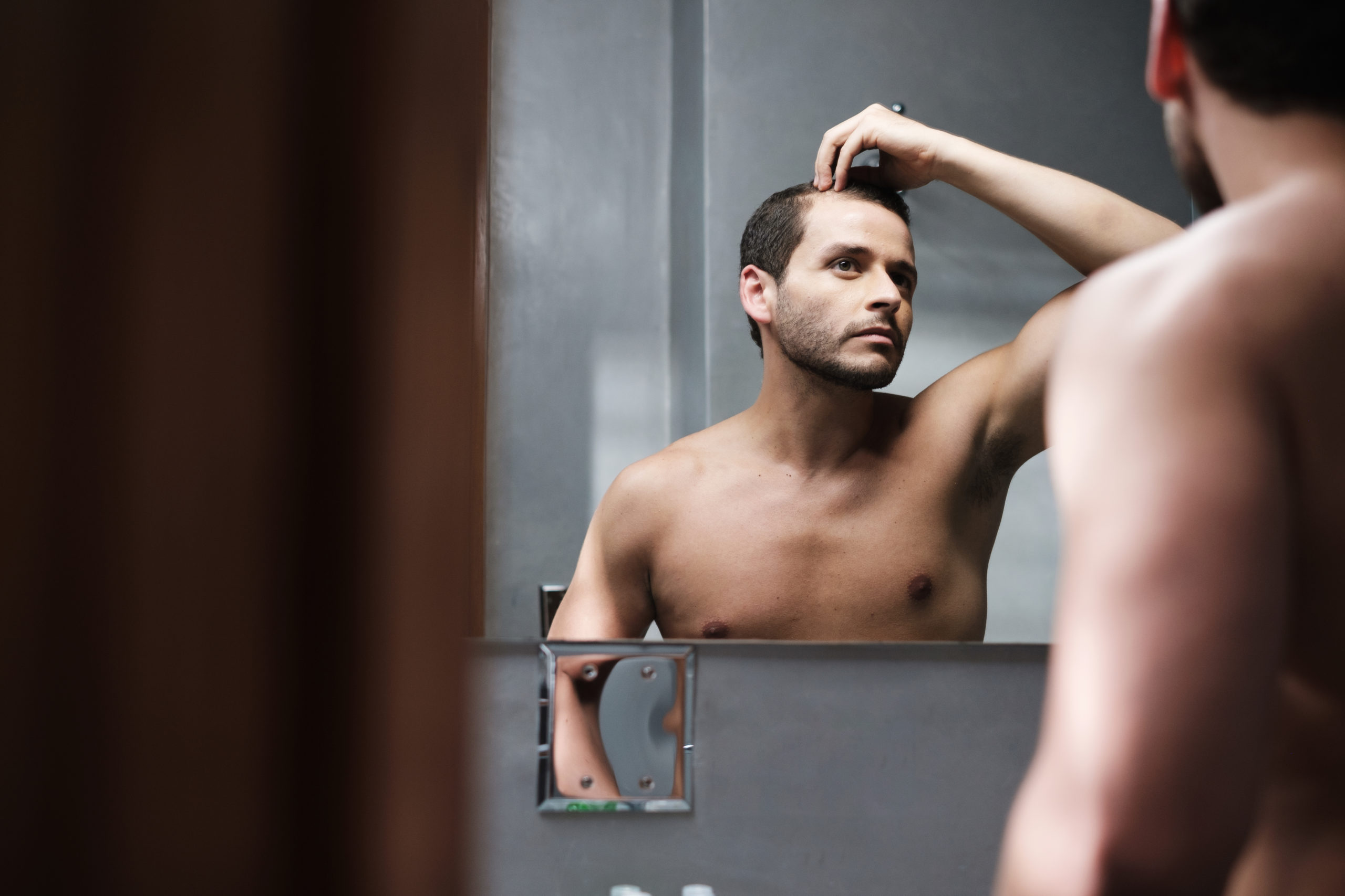 Man checking his hairline in a mirror